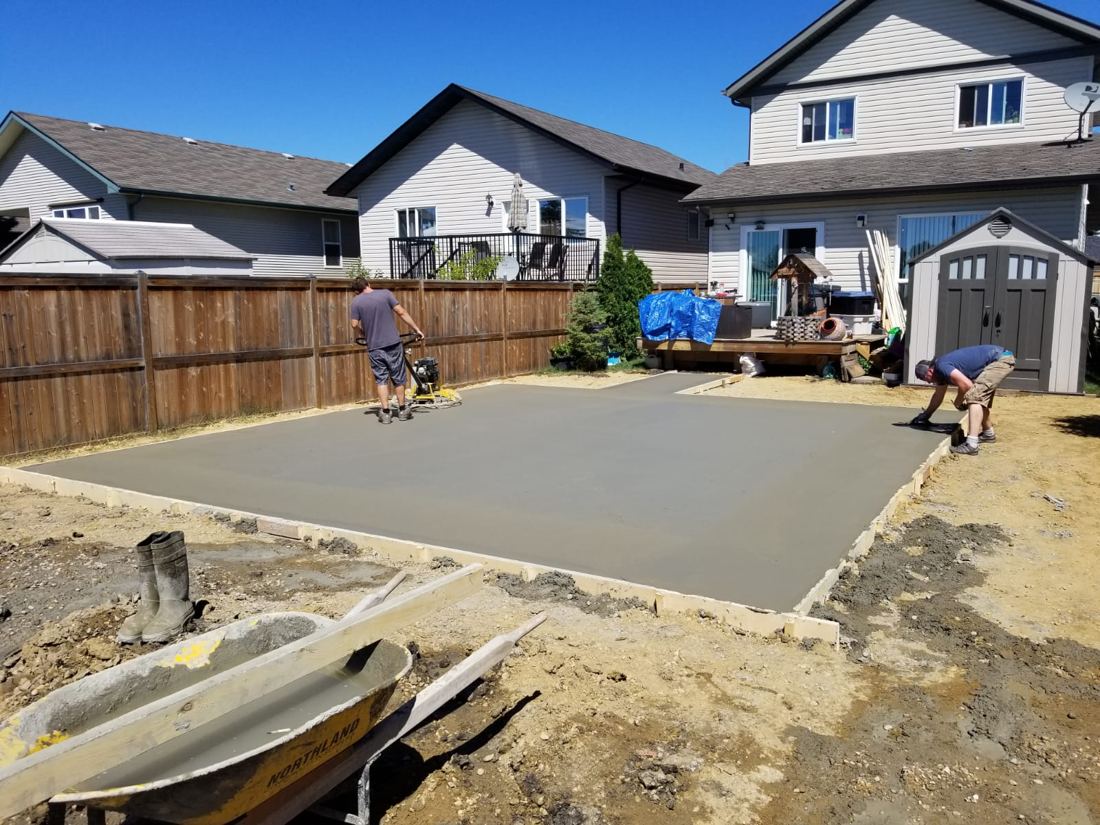 two men working in shorts house backyard patio cement in red deer