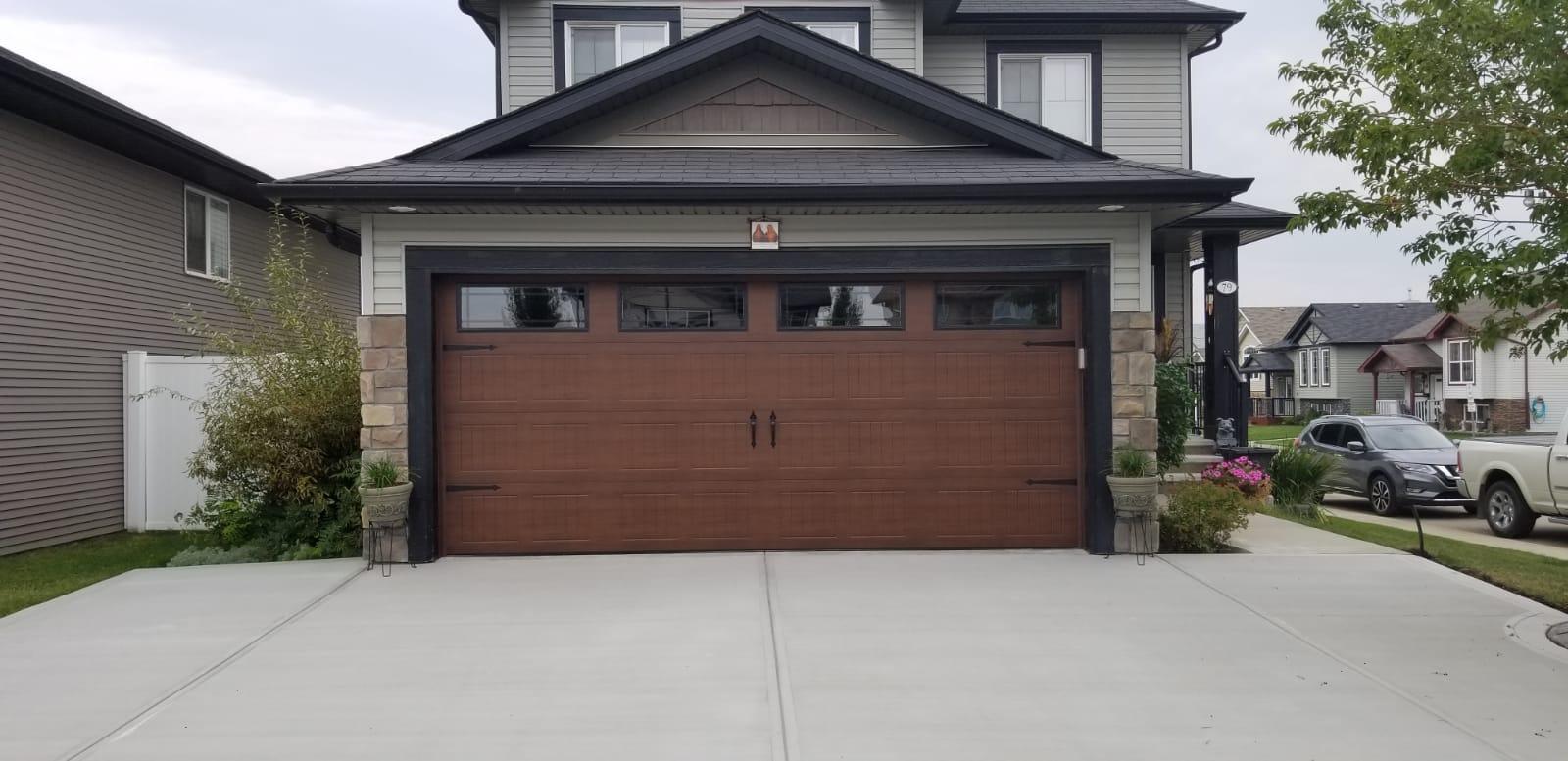 black roof house, brown wood garage, and paved driveway in red deer