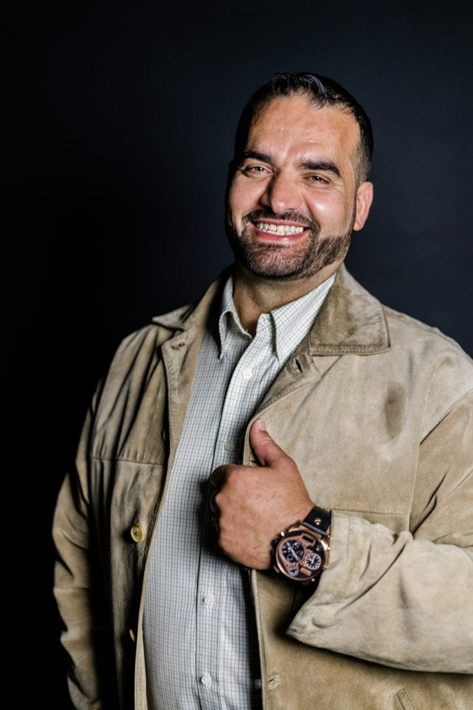 man smiling with brown jacket and watch