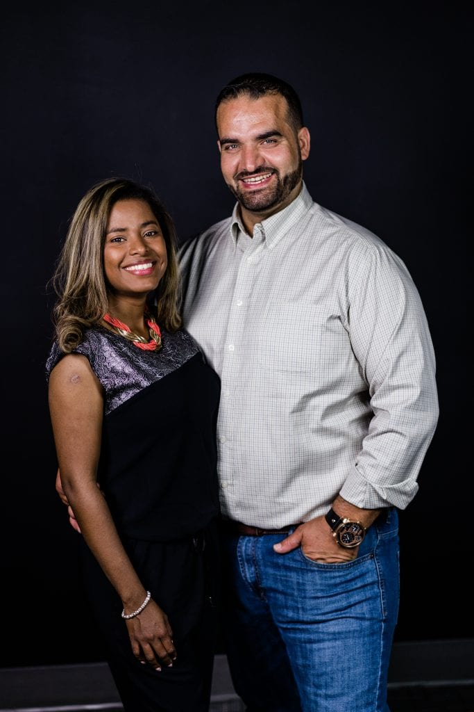 man smiling with grey dress shirt holding smiling woman in dark dress
